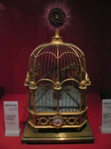 This is an image of an antique birdcage clock in a museum in the Forbidden City, Beijing, China. It appears to begold or bronze in color. The overall shape is a rounded rectangle; the apex of the cage has a rounded-trapezoid, closed cylinder about an inch in height, and on top of that is a short point. The top portion of the cage is slightly decorated with a single strand of gold or iron around the cage, similar to an umbrella, where there is are points that connect the fabric of the umbrella, and there are arches in between those points to connect the umbrella as a whole. In the center circumference is a similar strand, but slightly thicker. The points (as referred to earlier) is now decorated with small birds standing on a tiny circular platform with tiny ridges. These birds are made of the same material as the cage. Below those birds, the vertical bars are decorated with textured circles, like if polka dots were 3-D. These bars are also thicker than the ones above them. Finally, at the bottom, there is an octagonal shape. There are 4 wide sides like a square, and between them are shorter edges about 1/4 to 1/5 shorter than the sides mentioned earlier. These 4 edges connect to the 4 main sides. The octagon is decorated with another intricate design, possibly olive branches in a sine-cosine pattern. The clock is circular at the center of the front. There are 8 short legs below the cage, a pair under each of the shorter edges.