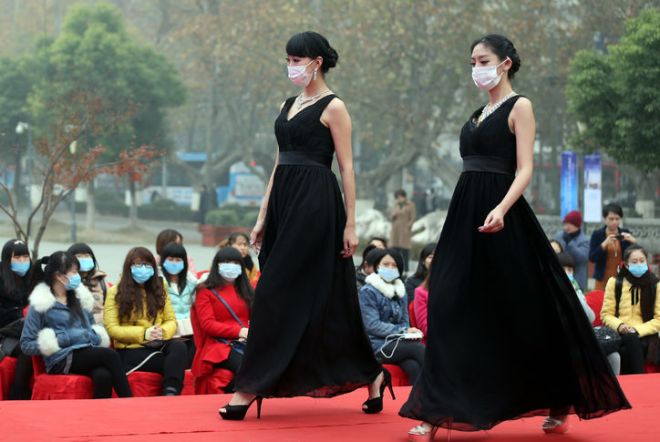 This image shows two Chinese models in Nanjing, China showing off jewelry but they are also wearing surgical masks because of terrible air pollution.  Spectators are also wearing surgical masks.